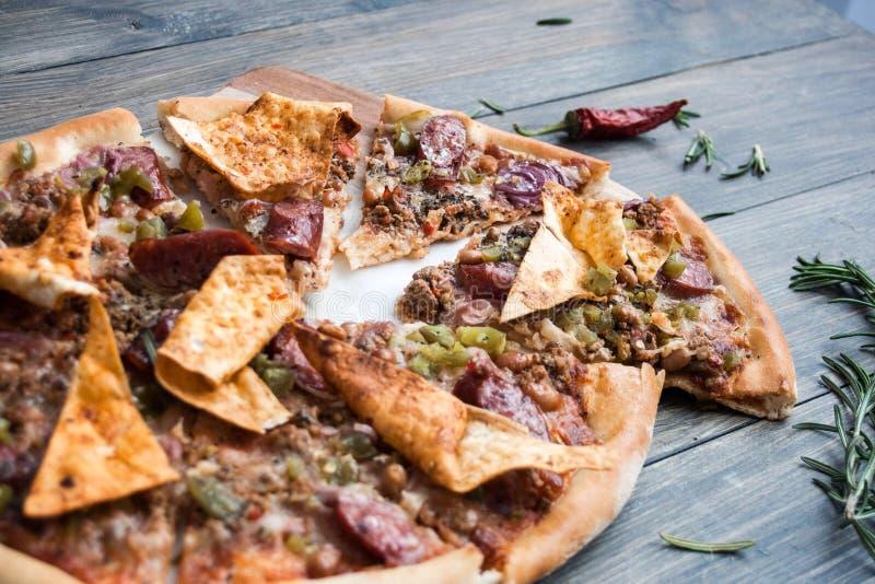 Mexicansk pizza med kött och peppar på en trätabell royaltyfri foto