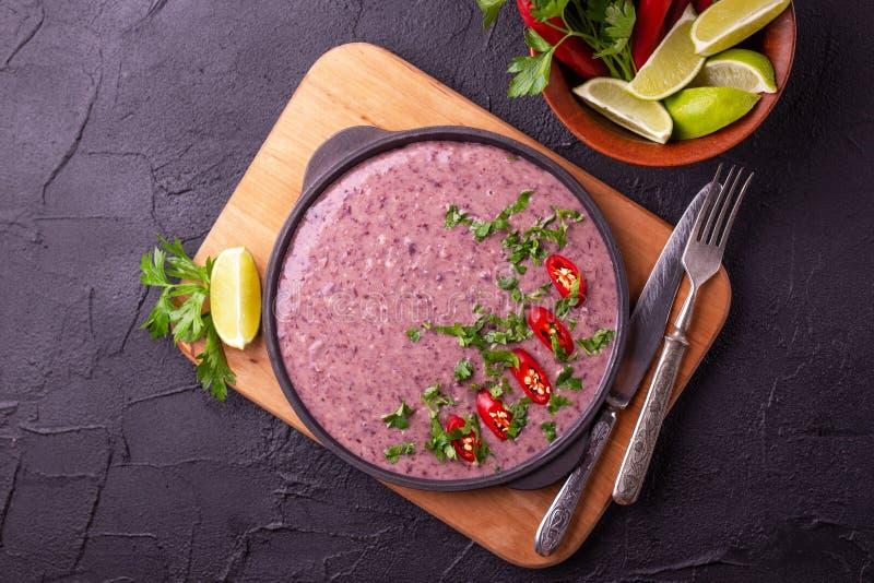 Mexicansk purésoppa för röd böna med limefrukt-, persilja- och chilipeppar royaltyfri foto
