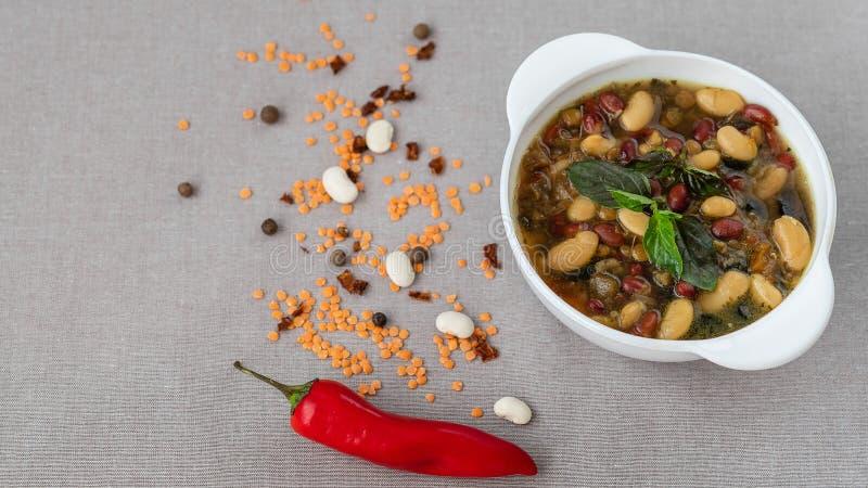 Mexicansk soppa av sju sorter av bönor med basilika, närbild, på en grå linnebakgrund som omges av röd peppar och bönor royaltyfri fotografi