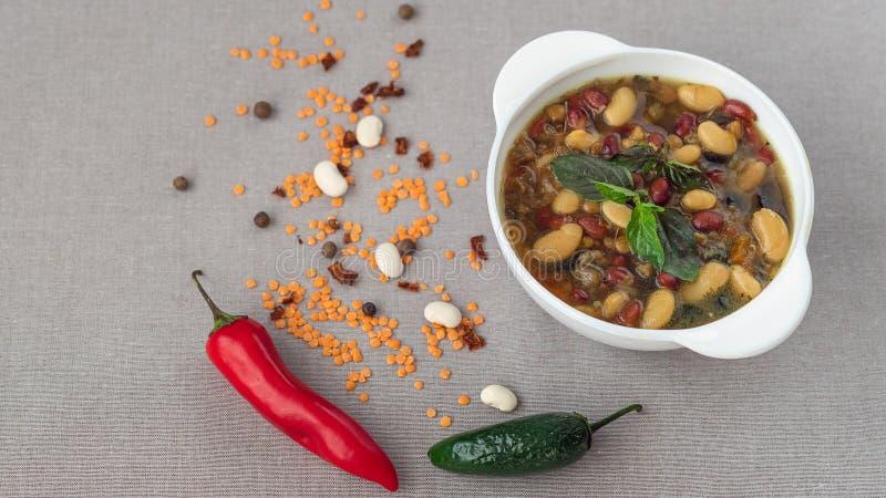Mexicansk soppa av sju sorter av bönor, närbild, på en grå linnebakgrund som omges av rött och paprikor och bönor royaltyfri bild
