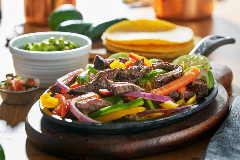 Mexicanska nötköttfajitas i järnkastrull med spanska peppar och guacamole på sidan royaltyfria foton