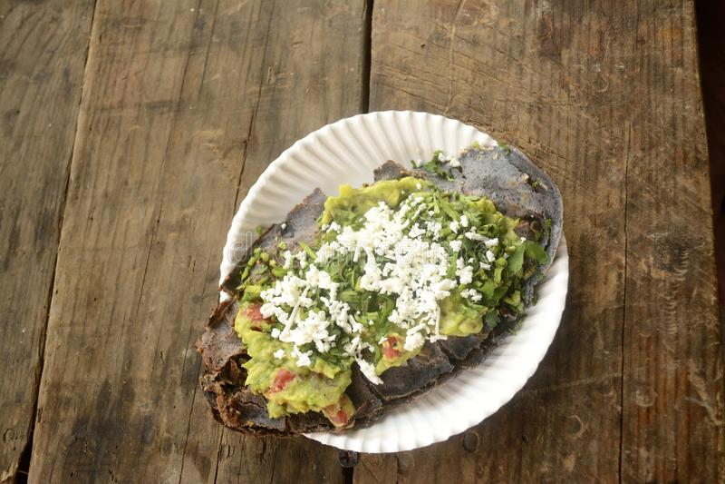 Mexicanska tlacoyos, en maträtt som göras med blått, konserverar och fyllde med stekte bönor eller bondbönor som är liknande till royaltyfria bilder
