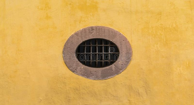 Mexicanskt kolonialt ovalt säreget fönster med den gula väggen royaltyfri foto