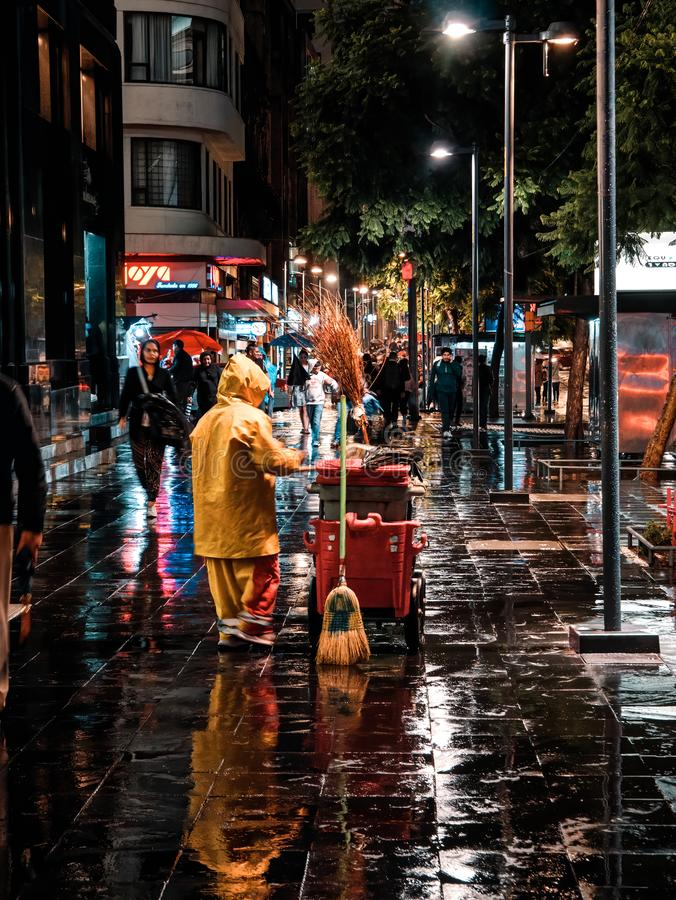 Woman sweeper cleans the sidewalk at night in Mexico City royalty free stock photo