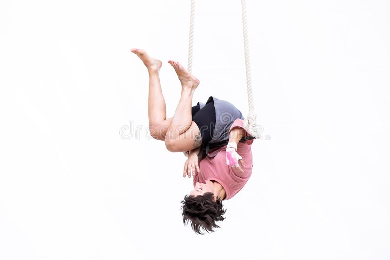 Trapeze artist hung upside down during her performance. MEXICO CITY - NOV 18, 2018: Young girl performs the acrobatic elements in the air trapeze on a white royalty free stock photography