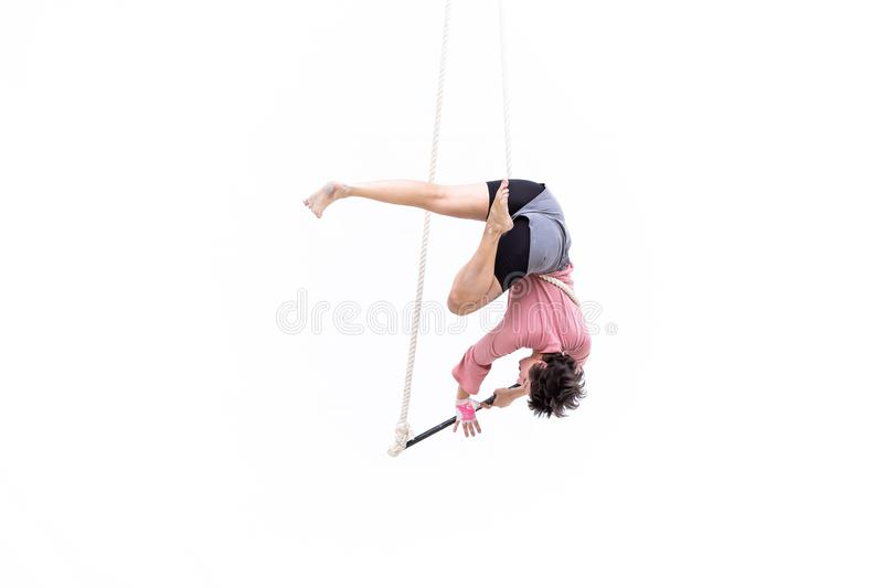 Trapeze artist hung upside down during her performance. MEXICO CITY - NOV 18, 2018: Young girl performs the acrobatic elements in the air trapeze on a white stock photo
