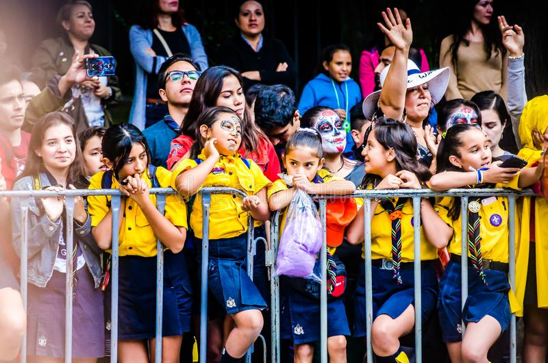 Mexico City, Mexico - October 27, 2018. Children in school uniform watching Celebration of Day of Dead parade, Dia de los Muertos stock photo