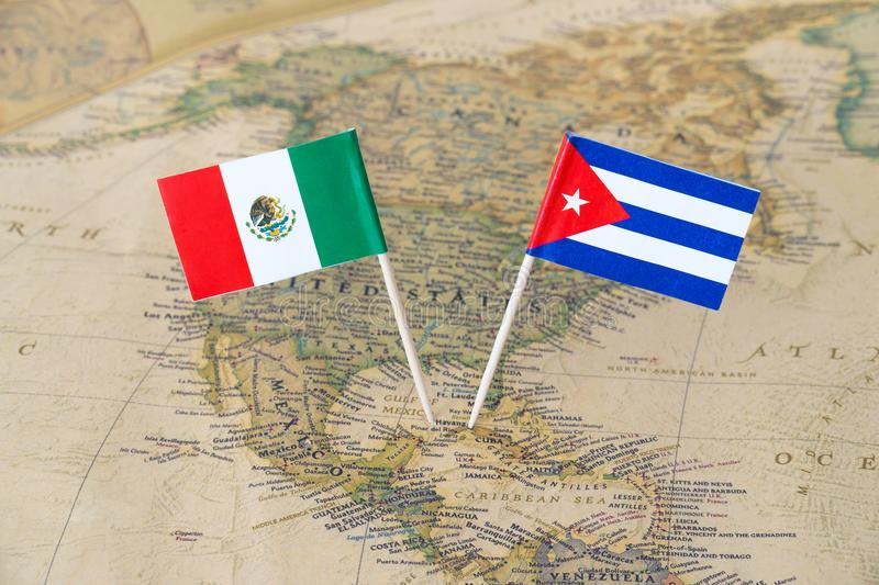 Mexico and Cuba flag pins on a world map, political relations concept. Paper flag pins of the Republic of Cuba and Mexico on a world map. Concept image of royalty free stock images