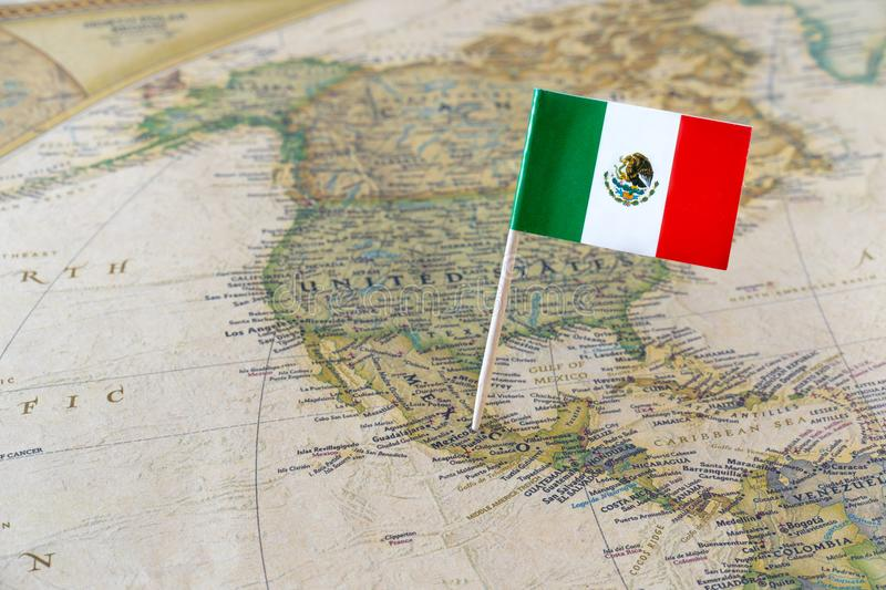 Mexico flag pin on map. Paper flag pin of Mexico on a map showing neigbouring countries. Officially the United Mexican States is a federal republic in the