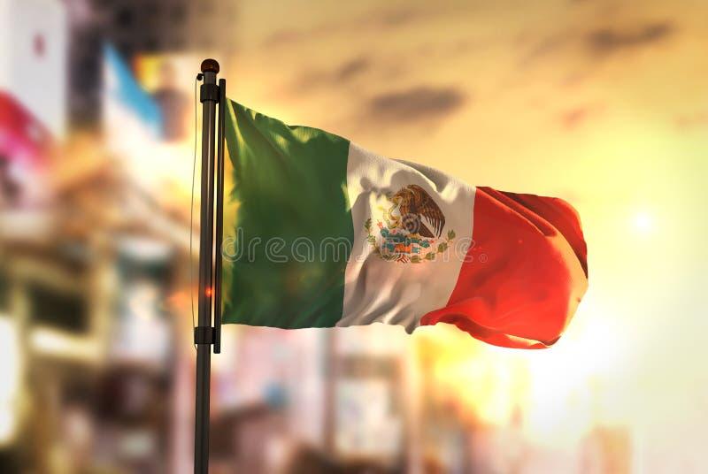 Mexico flagga mot suddig bakgrund för stad på soluppgångpanelljuset fotografering för bildbyråer