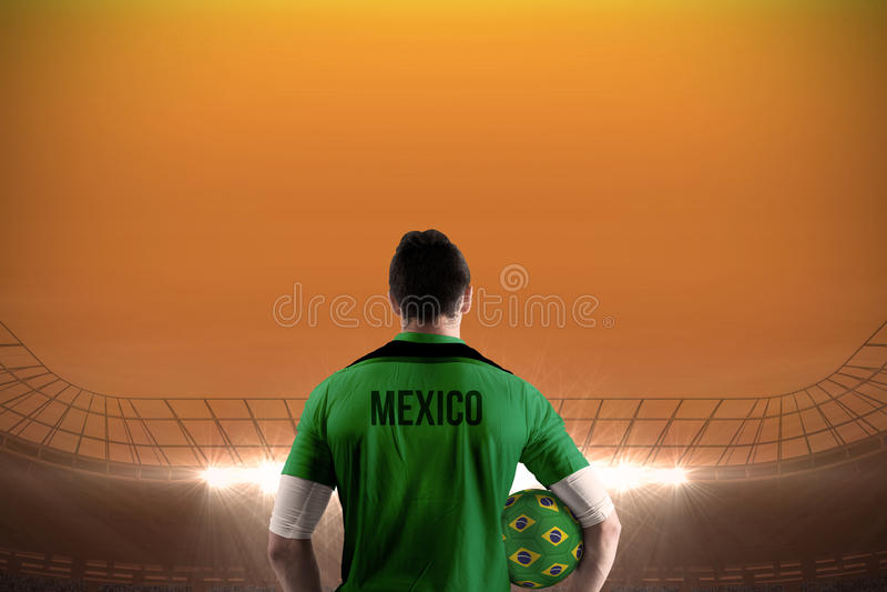 Mexico football player holding ball. Against large football stadium under orange sky royalty free stock photography