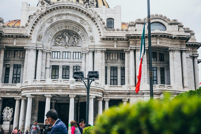 MEXICO - SEPTEMBER 20: Front view of the Palace of Fine Arts and the mexican flag in front of it. September 20, 2017 in Mexico City, Mexico stock image