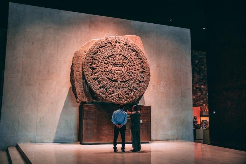 MEXICO - SEPTEMBER 28: Två personer som håller ögonen på den aztec kalendersten arkivfoton