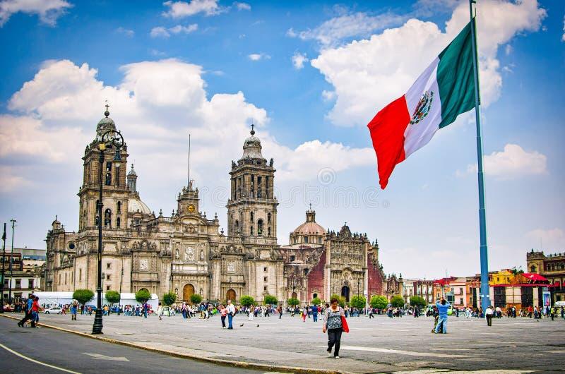 Mexico - stad, Mexico - April 12, 2012 Huvudsaklig fyrkant Zocalo med domkyrkan och den stora mexicanska flaggan arkivbild