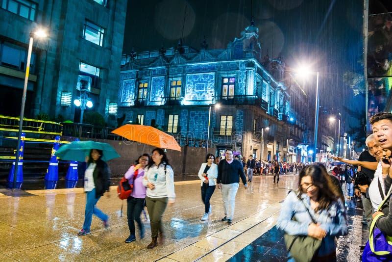 Mexico - stad, Mexico - Oktober 26, 2018 Nattfoto av den våta gatan med folk som går i regn arkivbild