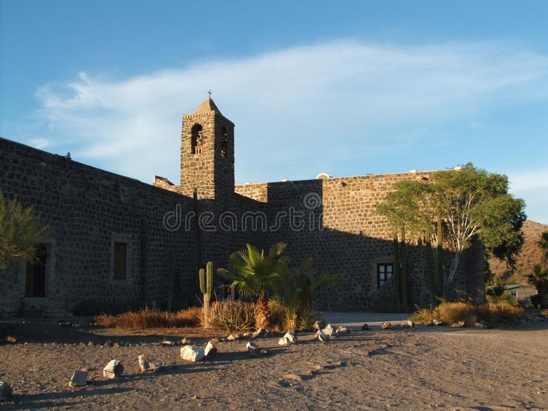 Mexico stone church during the day. Light blue sky is seen. Tall walls can be seen. No people are present. The sky is light blue stock images
