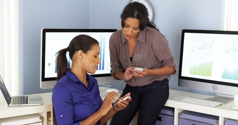 Mexikan- och afrikansk amerikanaffärskvinnor som tillsammans använder mobiltelefoner och arbete royaltyfria foton