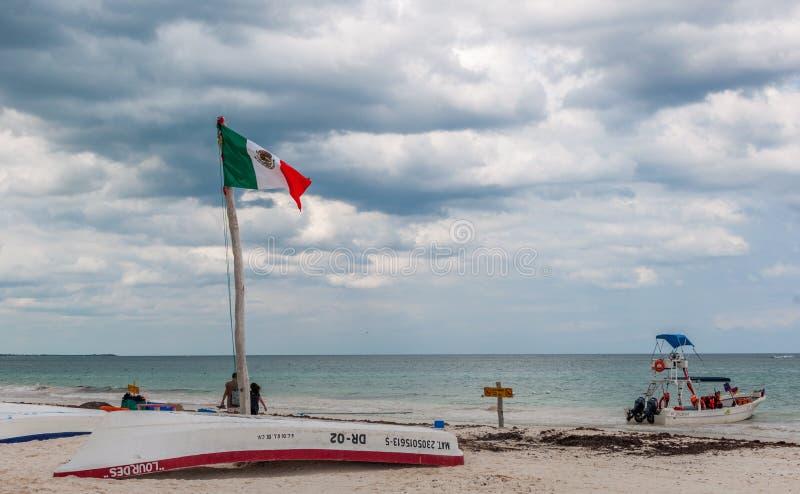 Mexikanische Flagge, die über einem umgedrehten Boot an Tulum-Strand aufgibt lizenzfreie stockbilder