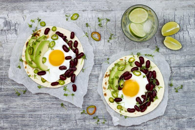 Mexikanische huevos rancheros Tacos Frühstück Tostadas mit schwarzen Bohnen, Avocado, Spiegelei, microgreens, sriracha Ketschup B stockfoto