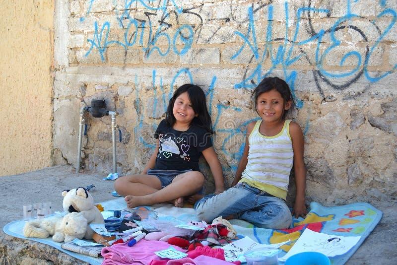 Mexikanische Mädchen, die auf dem Bürgersteig eines Armenviertels spielen lizenzfreies stockbild