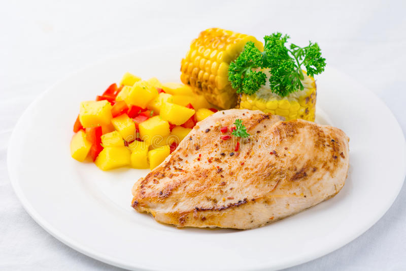 Mexikanische Mahlzeit: gegrillte Hühnerbrust, Mangosalsa und gegrillter Mais auf Platte stockfotos