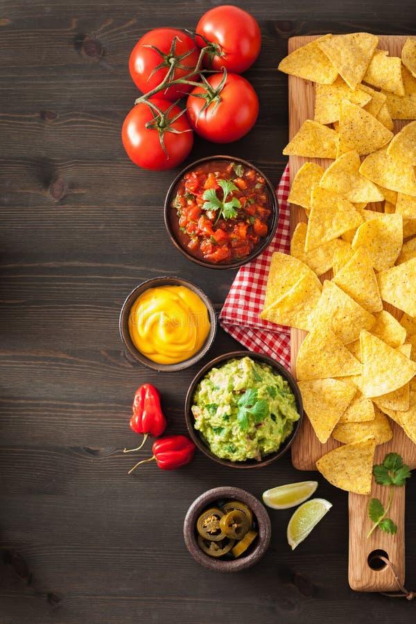 Mexikanische Nachos mit Guacamole-, Salsa- und Käsedip stockbilder