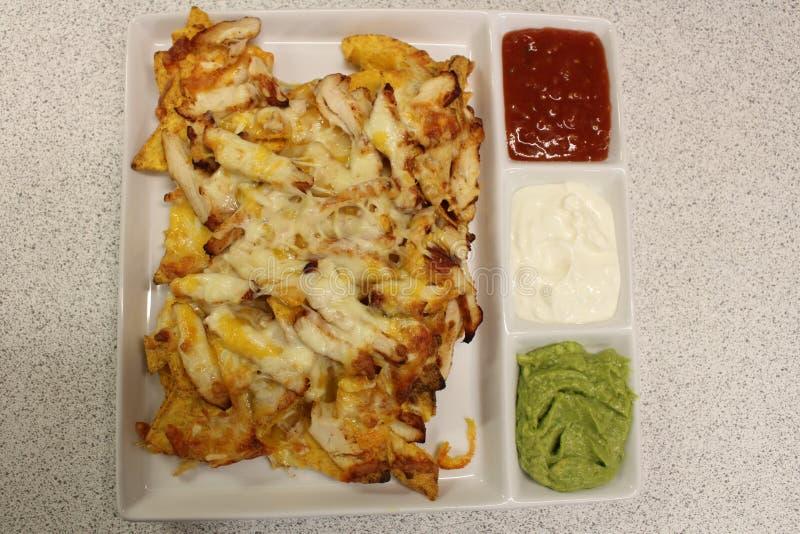 Mexikanische Nachos mit Huhn Nachos mit Corn chipen, Käse, Salsa, Guacamolen, Sauerrahm und Huhn Eine Platte von Tortilla Nachos lizenzfreies stockfoto