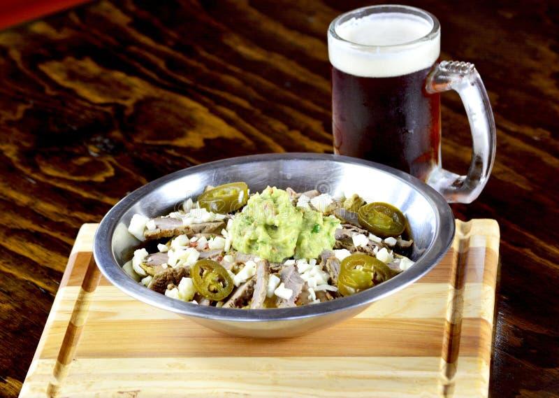 Mexikanische Nachos mit schwarzem Bier lizenzfreie stockfotos