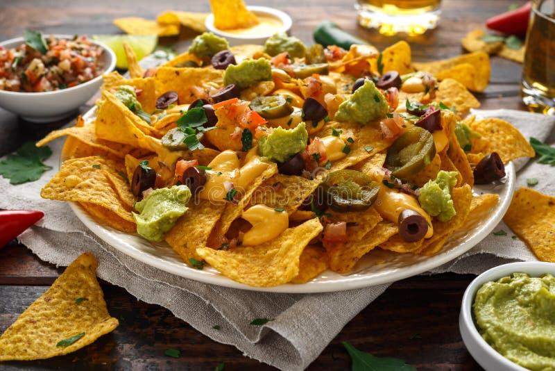 Mexikanische Nachostortilla-chips mit Oliven, Jalapeno, Guacamole, Tomaten Salsa, Käse dipand Bier lizenzfreie stockfotos