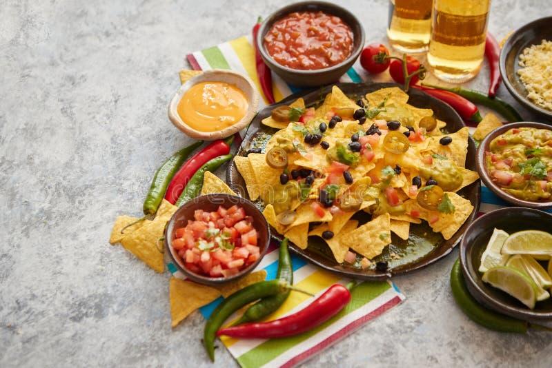 Mexikanische Nachostortilla-chips mit schwarzer Bohne, Jalapeno, Guacamole stockbilder