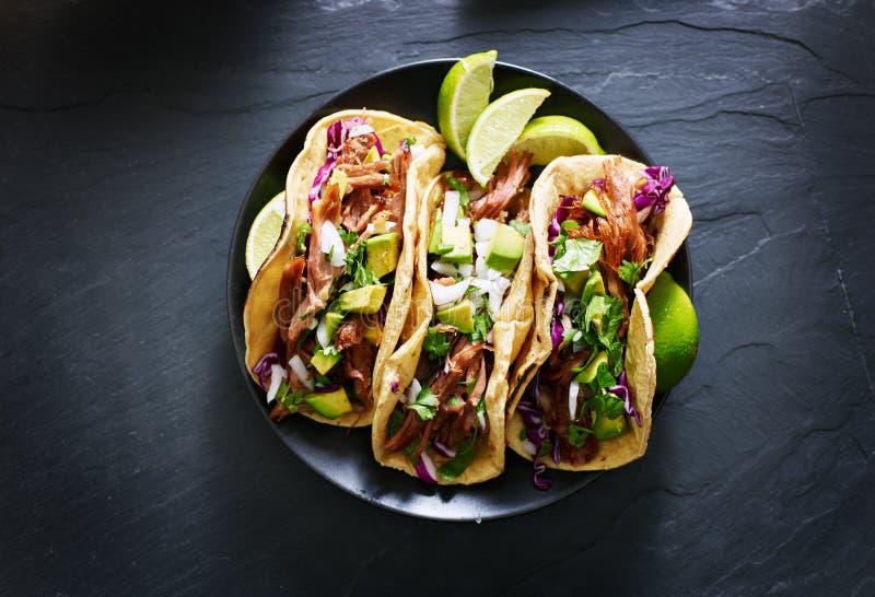 Mexikanische Straßentacos legen flach Zusammensetzung mit Schweinefleisch carnitas, Avocado, Zwiebel, Koriander und Rotkohl stockbilder