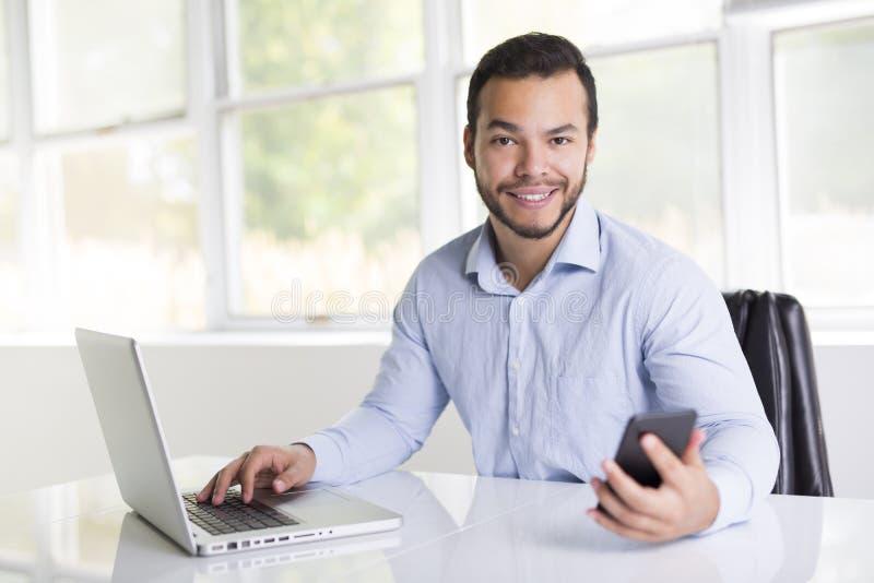 Mexikanischer attraktiver Geschäftsmann auf seinem 30s, das im modernen Innenministerium mit Computerlaptop arbeitet stockfoto