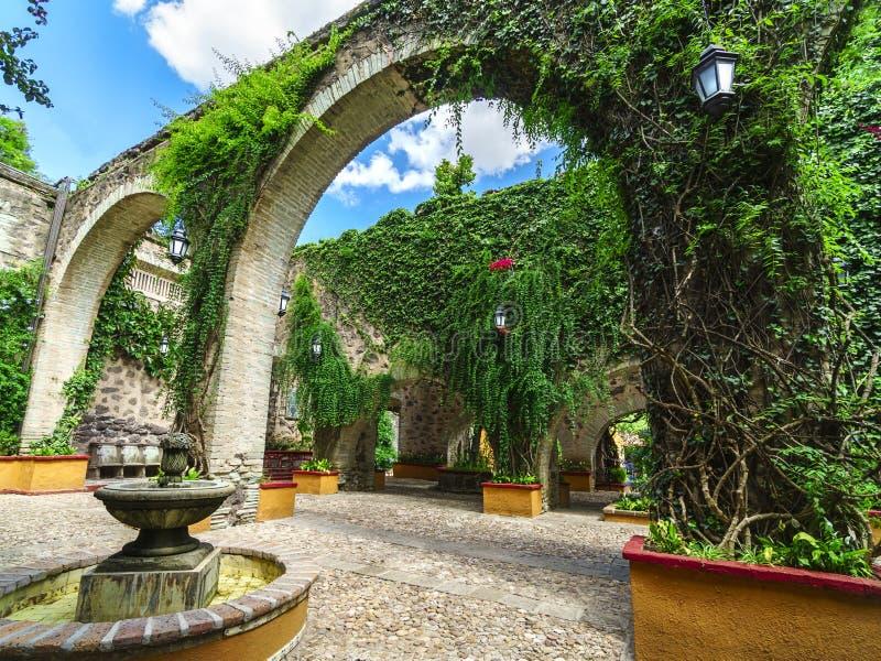 Mexikanischer Garten und Kolonialsteinbogen lizenzfreie stockbilder