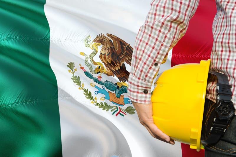 Mexikanischer Ingenieur hält gelben Schutzhelm mit dem Wellenartig bewegen des Mexiko-Flaggenhintergrundes Bau- und Geb?udekonzep lizenzfreies stockbild