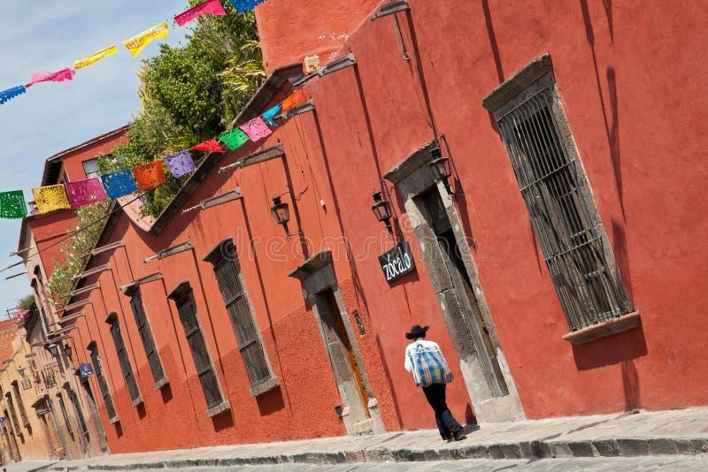 Mexikanischer Mann, der durch bunte Gebäude in Zocalo-Straße von San Miguel De Allende überschreitet lizenzfreies stockfoto