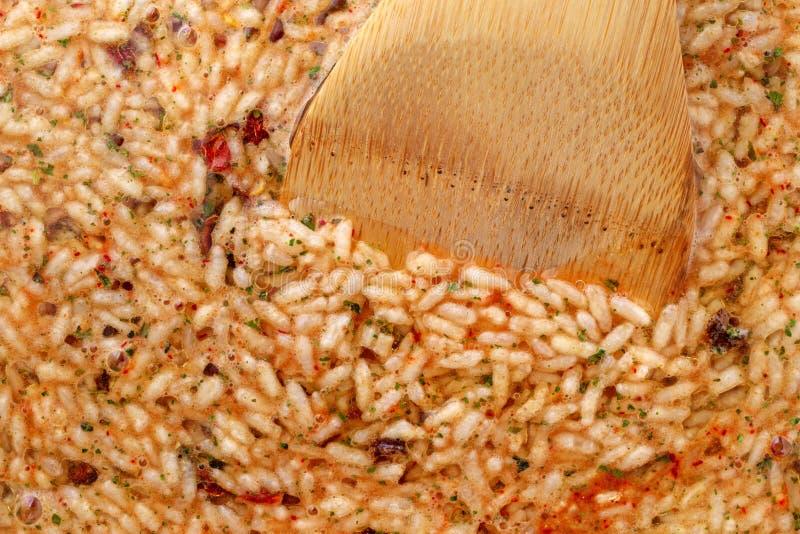 Mexikanischer Reis und Bohnen mischen in einer Bratpfanne mit einem hölzernen Löffel in der Nahrung lizenzfreie stockfotografie