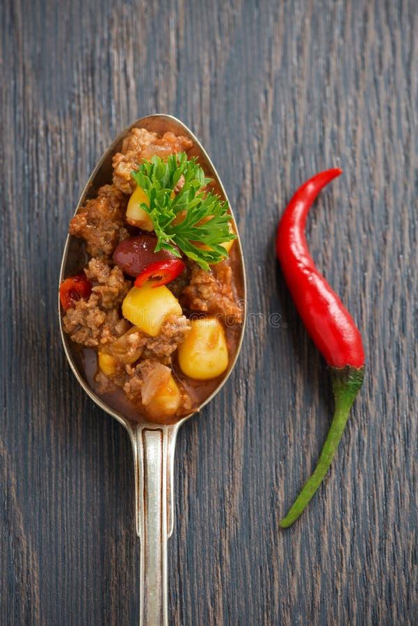 Mexikanischer Teller chili con carne in einem Löffel auf einem hölzernen Hintergrund lizenzfreie stockbilder