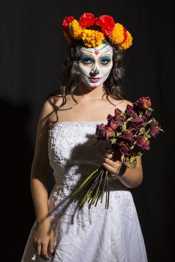 Mexikanisches catrina mit Blumenstrauß von Rosen auf schwarzem Hintergrund stockbilder