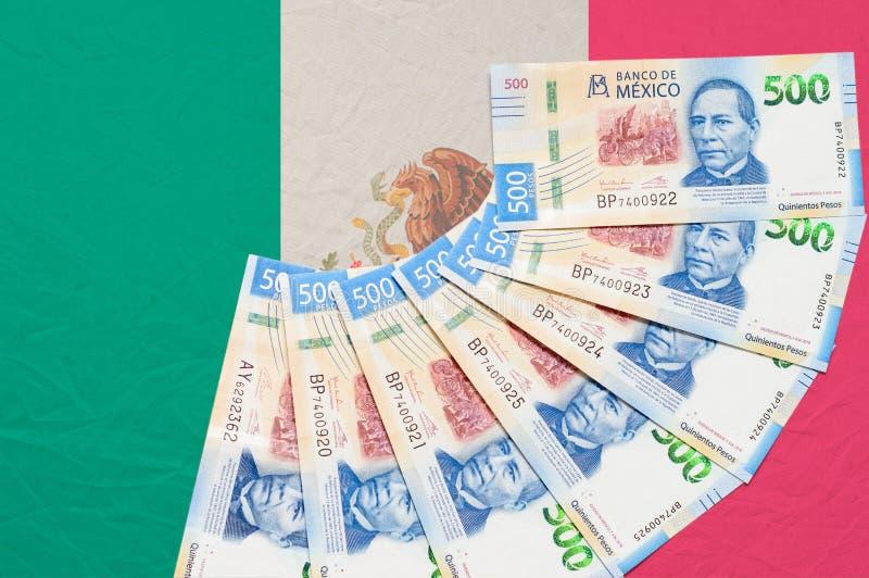 Mexikanisches Geld auf mexikanische Flagge lizenzfreie stockfotos