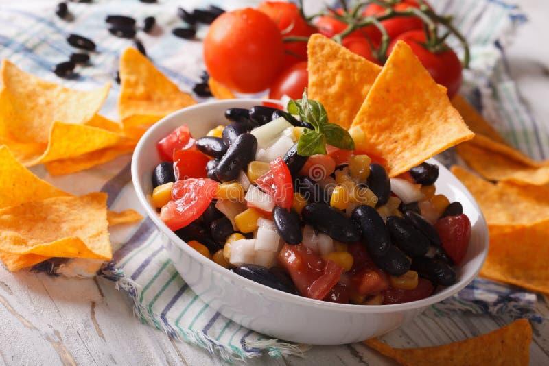Mexikanisches Lebensmittel: Salsa mit schwarzen Bohnen und Nachosnahaufnahme horizont lizenzfreie stockbilder