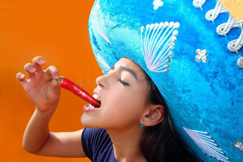 Mexikanisches Mädchen, das glühenden Paprikapfeffer isst lizenzfreies stockfoto