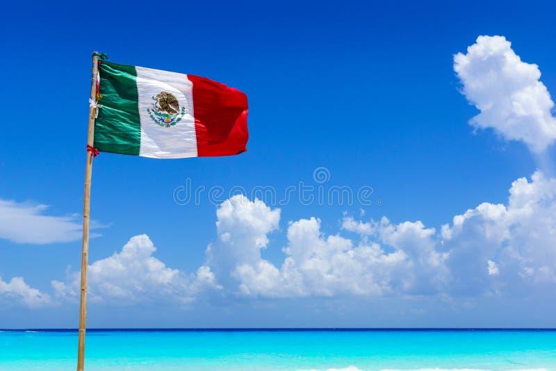Mexikanisches Staatsflaggefliegen im Wind auf einem erstaunlichen sandigen Strand vor Türkiswasser des karibischen Meeres, nahe C lizenzfreie stockfotografie