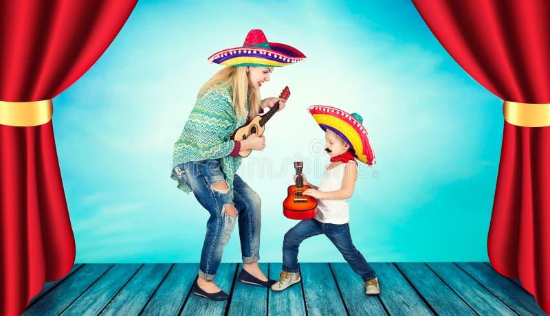 mexikansk deltagare En liten pojke i en sombrero spelar gitarren och sjunger en serenad för hans moder royaltyfria foton