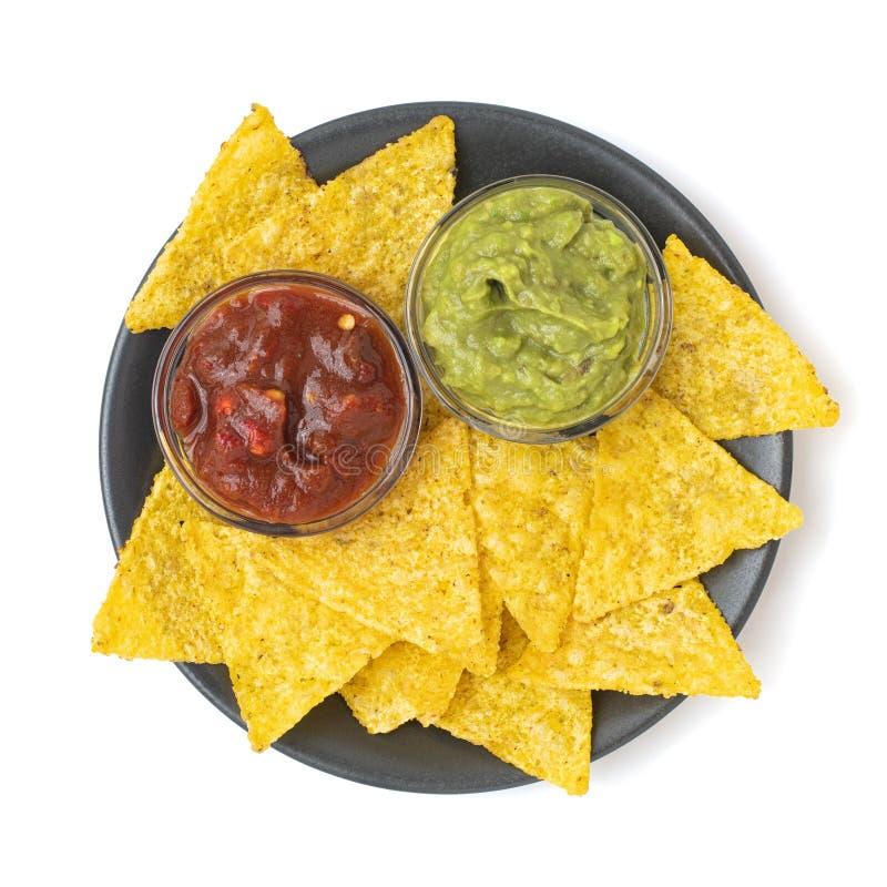 Mexikanska nachos tortilla chips med guacamol och salsa i mörk platta Isolerad på vit bakgrund Överkant royaltyfri bild