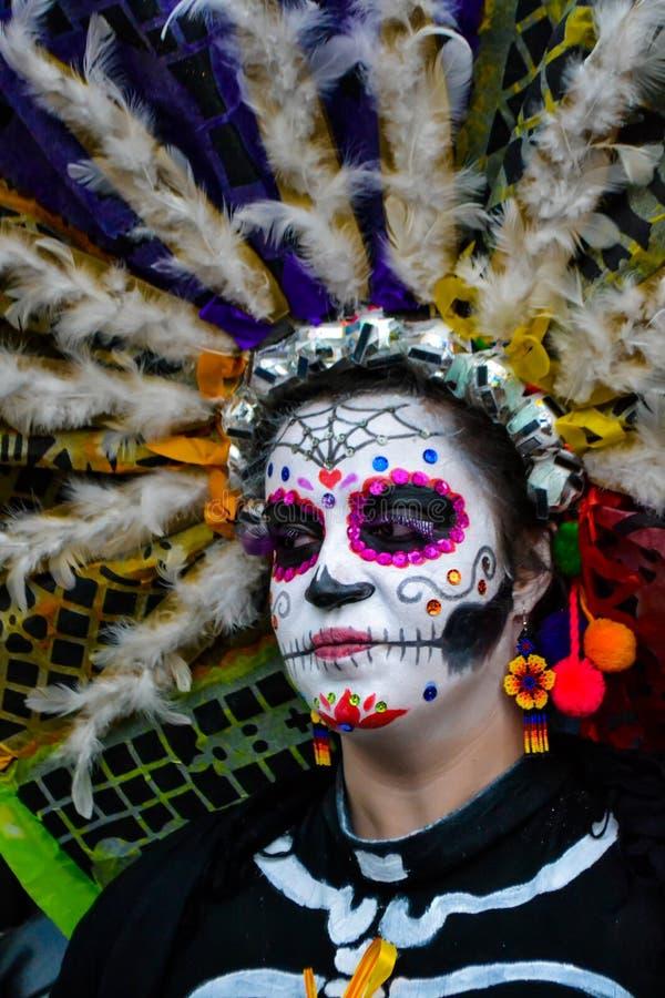 Mexiko City, Mexiko; Am 1. November 2015: Porträt einer Frau mit buntem Hut oder des penacho in der Verkleidung am Tag des toten  lizenzfreies stockbild