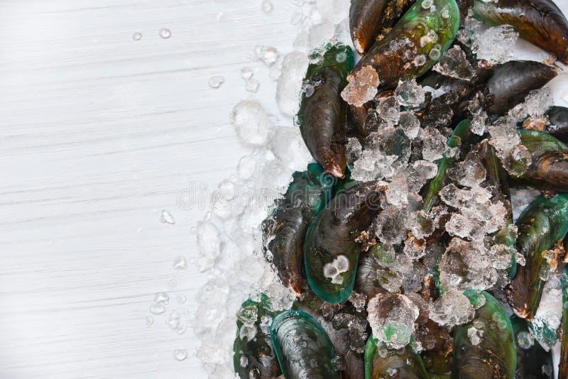 Mexilhão do marisco no gourmet verde cru fresco do oceano dos mexilhões do fundo do gelo no gelo e na vista superior de madeira b imagem de stock