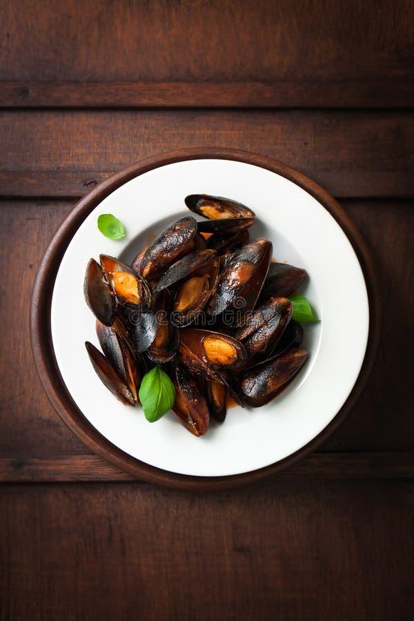 Mexilhões cozinhados caseiros com alho, molho de tomate, as ervas italianas, vinho branco e manjericão fresca em uma placa imagens de stock