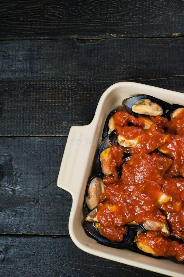 Mexilh?es crus com pasta de tomate no fundo preto, cozinhando imagem de stock