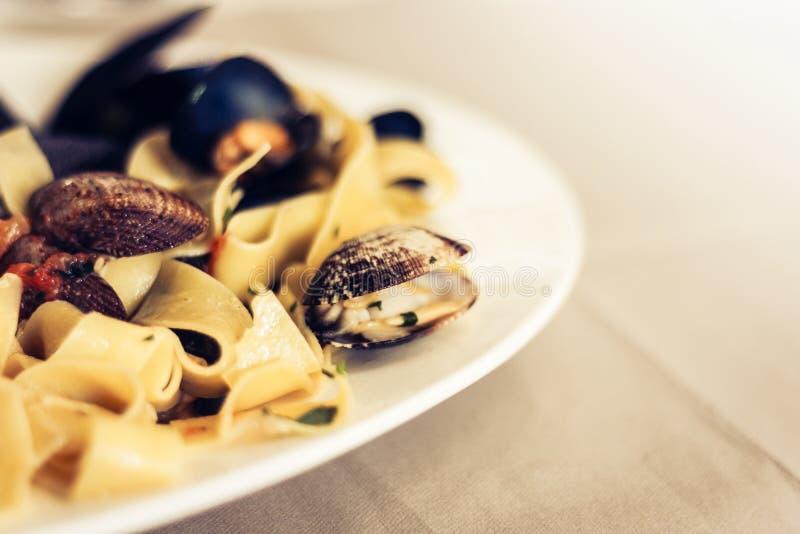 Mexilhões do desejo do linguine dos espaguetes da massa do marisco, moluscos, tomates de cereja, Parmesão fresco na placa branca  fotografia de stock royalty free