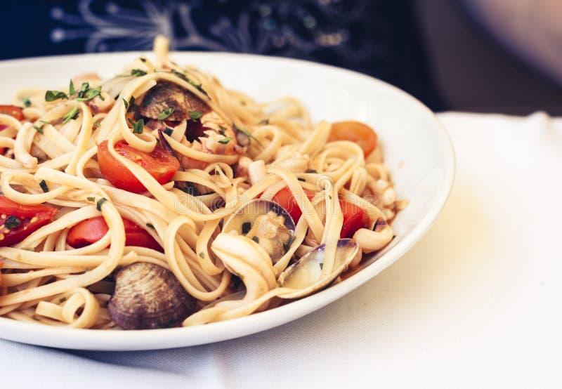 Mexilhões do desejo do linguine dos espaguetes da massa do marisco, moluscos, tomates de cereja, Parmesão fresco na placa branca  imagens de stock royalty free